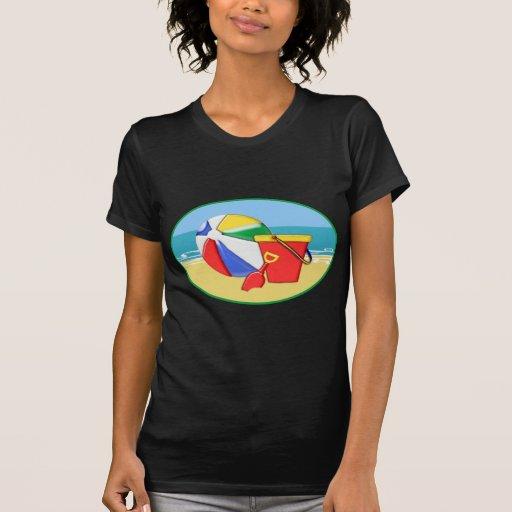 Pelota de playa, cubo y pala en la orilla camisetas