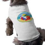 Pelota de playa, cubo y pala en la orilla camisa de perro
