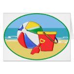 Pelota de playa, cubo y pala en la orilla felicitación