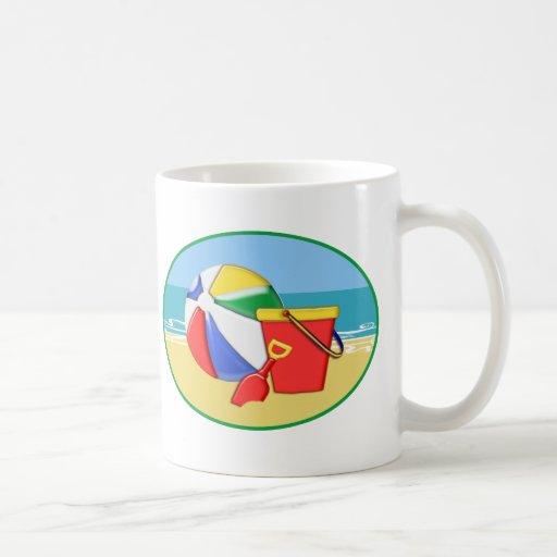 Pelota de playa, cubo y pala en la orilla tazas de café