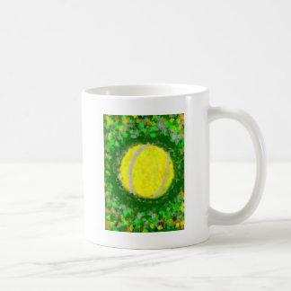 Pelota de tenis en una hierba taza