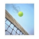 Pelota de tenis que fuma que vuela sobre red libretas para notas