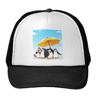 Penguins standing under umbrella trucker hat