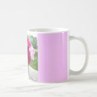 Peonies rosados y rojos en café del florero o taza
