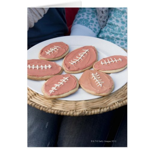 People holding plate of football cookies greeting card