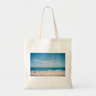 People on a beach in a beautiful weather budget tote bag