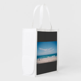 People on a beach in a beautiful weather reusable grocery bags