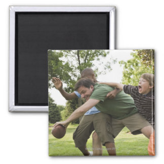 People tackling while playing football magnet