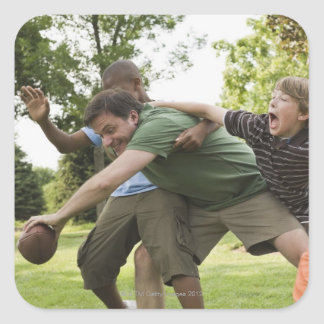 People tackling while playing football square sticker