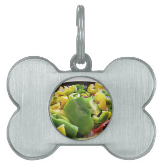 Peppers and onions in the cooking pan on white bac pet ID tag