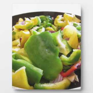 Peppers and onions in the cooking pan on white bac plaque