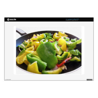 Peppers and onions in the cooking pan on white bac skin for laptop