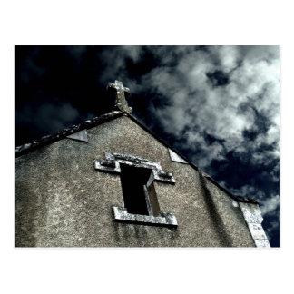 Pequeña iglesia gótica con el cielo nublado postal