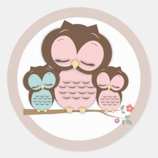 Pequeña mamá dulce y búhos gemelos del bebé en una pegatina redonda
