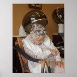 Pequeña mujer mayor dormida debajo del secador de  poster