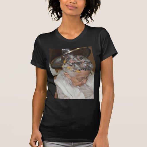 Pequeña mujer mayor dormida debajo del secador de t shirt