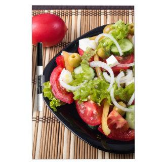 Pequeña porción de ensalada vegetal del tomate tablero blanco