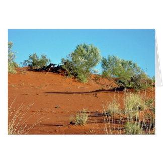Pequeñas plantas en dunas de arena rojas tarjetón