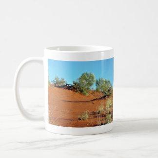 Pequeñas plantas en dunas de arena rojas taza