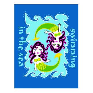Pequeñas sirenas que nadan en el mar postales