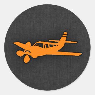 Pequeño aeroplano anaranjado etiqueta redonda