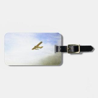 Pequeño avión con el cielo azul etiquetas maleta
