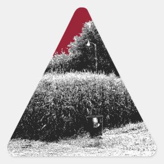 Pequeño campo de maíz con el cielo rojo oscuro pegatina triangular