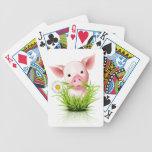 Pequeño cerdo rosado en hierba barajas de cartas