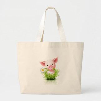 Pequeño cerdo rosado en hierba bolsas lienzo