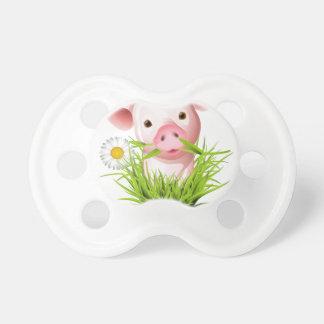 Pequeño cerdo rosado en hierba chupetes de bebe