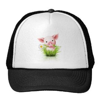 Pequeño cerdo rosado en hierba gorra