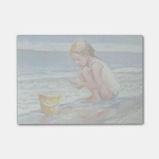 Pequeño chica del beachcomber con el cubo amarillo post-it notas