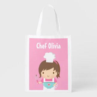 Pequeño chica lindo del panadero del cocinero bolsas para la compra