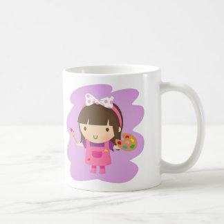 Pequeño chica lindo del pintor del artista en el taza de café