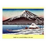 Pequeño edificio nevado en la costa tarjetas postales