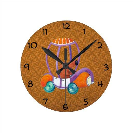 Pequeño individuo lindo en coche lindo relojes de pared