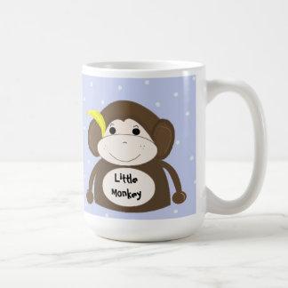 Pequeño mono con un plátano amarillo tazas de café