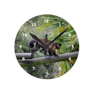 pequeño mono que corre a través de la verja reloj redondo mediano