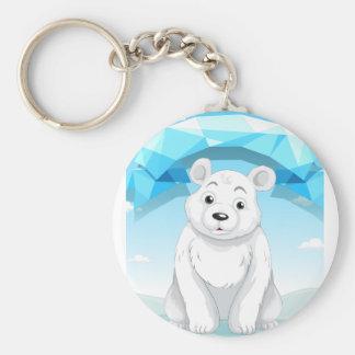 Pequeño oso polar que se sienta en el hielo llavero redondo tipo pin