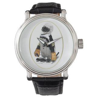 Pequeño pingüino del jugador de hockey de la relojes