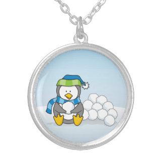 Pequeño pingüino que se sienta con las bolas de collar plateado
