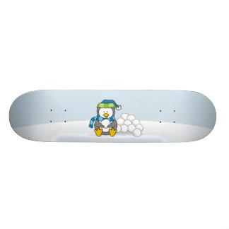 Pequeño pingüino que se sienta con las bolas de skateboards