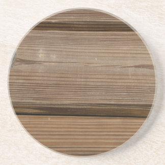 Pequeño vidrio en tablones marrones de madera del  posavasos cerveza