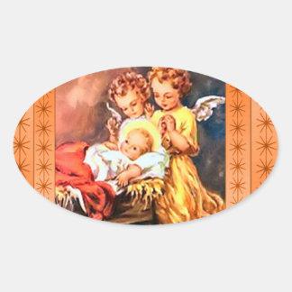 Pequeños ángeles en el pesebre calcomania óval