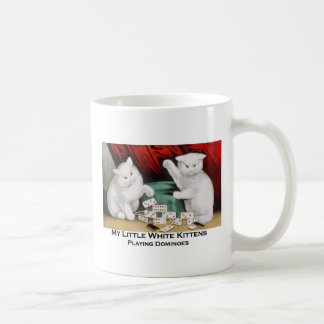 Pequeños gatitos blancos que juegan dominós tazas de café