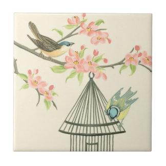 Pequeños pájaros encaramados en una rama y en un azulejo cuadrado pequeño