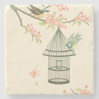 Pequeños pájaros encaramados en una rama y en un posavasos de piedra