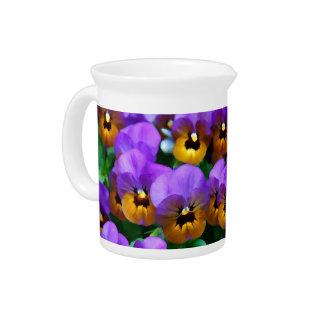 Pequeños pensamientos púrpuras arreglados en oro a jarra de beber