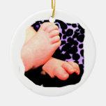 Pequeños pies del bebé, fondo púrpura del leopardo ornamente de reyes
