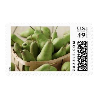 Peras verdes en cestito y tabla de madera sellos
